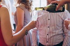 Champagne se renversant de serveur en verre personnes élégantes tenant le glasse Photographie stock