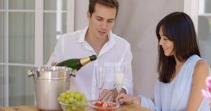 Champagne se renversant de sourire de jeunes couples à boire Image stock