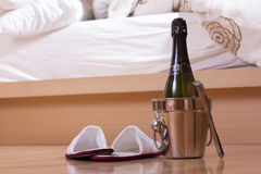 Champagne and shoes close to a bed Stock Photos