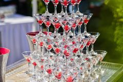 Champagne slide. Pyramid or fountain made of champagne glasses with cherry. stock photos
