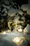 Champagne on snow. Two glasses with champagne on snow in an environment of candles and coniferous branches at night in wood stock images