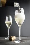 Champagne som fylls in i exponeringsglas arkivfoto