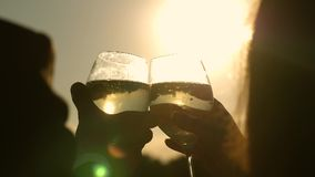 Champagne sparkles and foams in sun. couple in love holding wine glasses with sparkling wine on background of sunset. Close-up. teamwork of loving couple stock footage