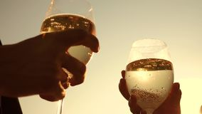Champagne sparkles and foams in sun. couple in love holding wine glasses with sparkling wine on background of sunset. Closeup. teamwork of loving couple stock footage