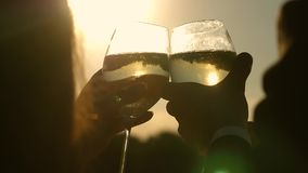 Champagne sparkles and foams in sun. couple in love holding wine glasses with sparkling wine on background of sunset. Close-up. teamwork of loving couple stock video footage