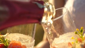 Champagne sparkles and foams in the sun. teamwork of a loving couple. celebrating success and victory. pouring sparkling. Wine from bottle into transparent wine stock video footage