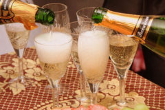 Champagne spill on glasses Stock Images