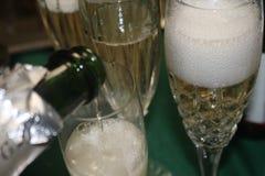 Champagne sprudelt in einem Kristallglas mit mehr Champagner, der ausgelaufen wird Stockfoto