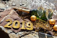 Champagne on a stony beach by the sea, New Year celebrate preparation concept. royalty free stock photography