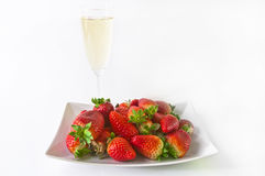 Champagne and strawberries. Glass of champagne with plate full of strawberries behind isolated on a white background Stock Photography