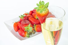 Champagne and strawberries. Glass of champagne with plate full of strawberries behind on a white background Royalty Free Stock Photography