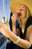 Champagne & Strawberries. A stunningly beautiful and wealthy young blond woman sitting on the deck of her yacht in a marina eating strawberries and drinking Stock Photos