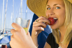 Champagne & Strawberries on De. A stunningly beautiful and wealthy young blond woman sitting on the deck of her yacht in a marina eating strawberries and Royalty Free Stock Photography