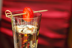 Champagne and strawberry. With a toothpick with a red background Royalty Free Stock Images