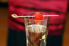 Champagne and strawberry. With a toothpick with a red background Stock Photography