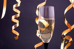 Champagne and streamers. Champagne in a glass and streamers, with copyspace Stock Photo