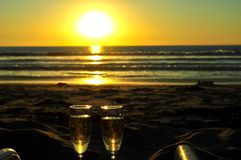 Champagne Sunset. Two Champagne Glasses full of bubbly on the beach with a gorgeous Yellow Sunset in against the Ocean royalty free stock images