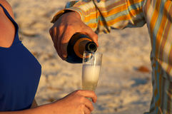 Champagne at sunset. A man is pouring champagne into a woman's glass on the beach at sunset. Close up on hands, bottle and glass Royalty Free Stock Photos
