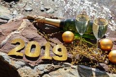Champagne sur une plage pierreuse par la mer, nouvelle année célèbrent le concept de préparation Photographie stock libre de droits