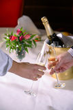 A Champagne Toast. A couple touching champagne glasses in a toast to a special occasion with an ice bucket, champagne bottle and flower bouquet in the background stock photo