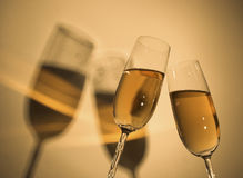 Champagne Toast 2. Champagne toast.  Golden hue.  Glasses cast a distinct shadow with a rainbow of golden light reflected in the shadows Royalty Free Stock Photos