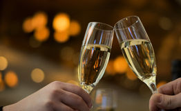 Champagne toast. Champagne, some glasses, and a Dom Pérignon and Clicquot bottle behind. Bokeh background. Restaurant scene Royalty Free Stock Photo
