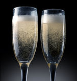 Champagne toasting. Two champagne glasses being  on black Royalty Free Stock Images