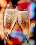 Champagne toasting. Two champagne glasses toasting bright lights Stock Images