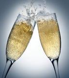Champagne toasting. Two champagne glasses toasting splashing Royalty Free Stock Photos