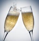 Champagne toasting. Two champagne glasses toasting splashing Stock Photo
