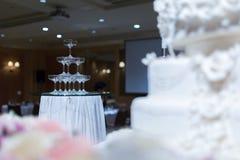 Champagne-toren en huwelijkscake voor stock fotografie