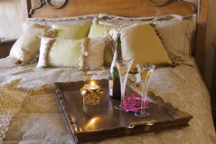 Champagne for Two. Luxury bedroom with pillows and tray with champagne and candle Royalty Free Stock Photo