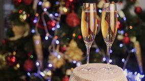 Champagne in two glasses  the christmas background. Two Champagne Glasses On Defocused Background Living Room With Christmas Tree stock video