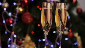 Champagne in two glasses  the christmas background. Two Champagne Glasses On Defocused Background Living Room With Christmas Tree stock footage