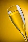Champagne in un vetro su priorità bassa dorata Fotografia Stock Libera da Diritti