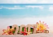 Champagne und die Aufschrift 2017 im Sand, verziert mit tropischen Blumen auf einem Hintergrund von Meer Lizenzfreie Stockbilder
