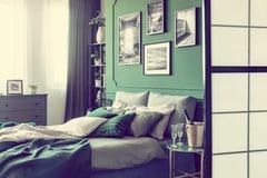 Champagne und Gläser auf nightstand Tabelle nahe bei Königgrößenbett mit luxuriöser Bettwäsche im eleganten Hotelzimmer lizenzfreies stockfoto
