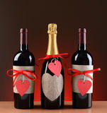 Champagne and Wine Bottles Decorated For Valentine. S Day. The bottles have red ribbons and heart shaped tags. Vertical format on a light to dark red background royalty free stock photo