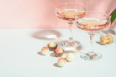 Champagne or wine in elegant glasses on a pink background bright light. Copy space. Selective focus. stock photo