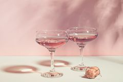 Champagne or wine in elegant glasses on a pink background bright light. Copy space. Selective focus. Horizontal frame royalty free stock image
