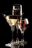 Champagne wine and martini glasses. Over black background Royalty Free Stock Images