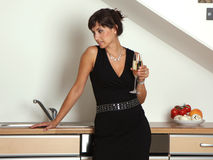 Champagne woman. Woman in kitchen on a home party with champagne royalty free stock photography