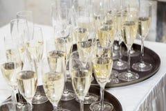 Champagne wordt gegoten door het glas Feestontvangst stock afbeeldingen