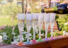 Champagne wordt gegoten van een fles in veelkleurige glazen in het midden van een park op een zonnige dag stock foto's
