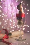 Champagneexponeringsglas fyllde med julleksaker, gåvaasken med den röda pilbågen som antyder på kommande ferier och nya år beröm, Royaltyfria Foton