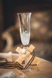 Champagneexponeringsglas med en bröllopgarnering och band Royaltyfri Foto