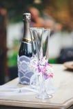 Champagneexponeringsglas med en bröllopgarnering och en flaska av champagn Arkivfoto