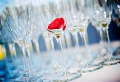 Champagneexponeringsglas med en jordgubbe i ett av dem Arkivbild
