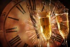 Champagneexponeringsglas mot den ferieljus och klockan på midnig royaltyfri fotografi