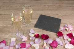 Champagneexponeringsglas och blommapelats Royaltyfri Fotografi
